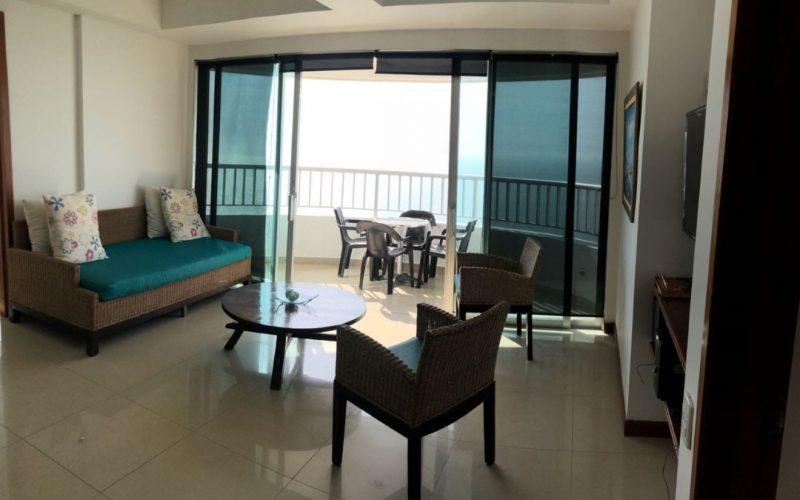 sala con tres sillas en mimbre y al fondo comedor exterior ubicado en balcon apartamento para alquiler por dias en cartagena