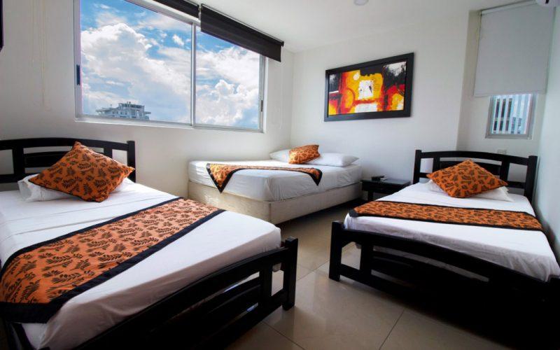 habitacion con dos camas sencillas en madera negra y un colchon sobre un somier blanco con ventana amplia e iluminada