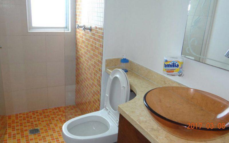 baño pequeño con inodoro blanco y ducha con azulejos naranja
