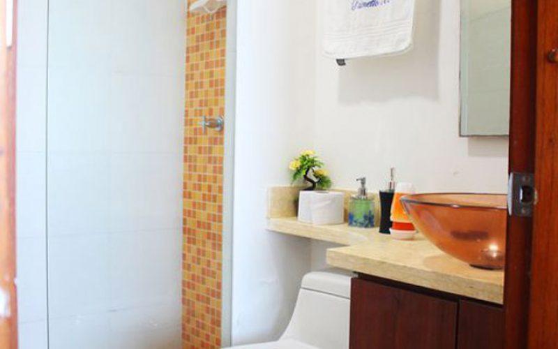 baño con inodoro blanco y ducha con azulejos naranja en edificio palmetto
