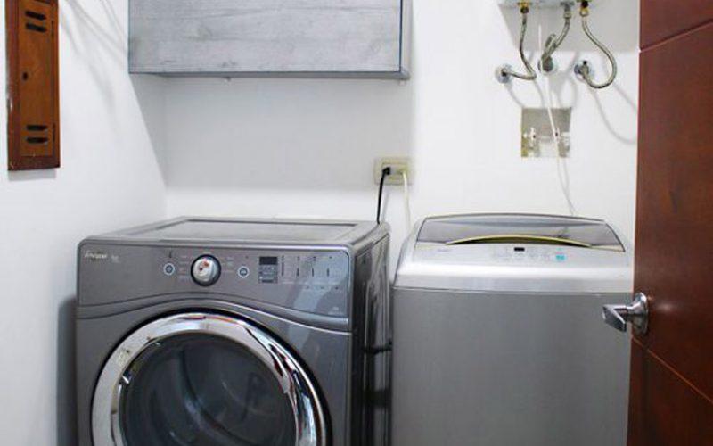 zona de lavado con lavadora de carga superior y secadora de carga frontal encima un calentador de gas
