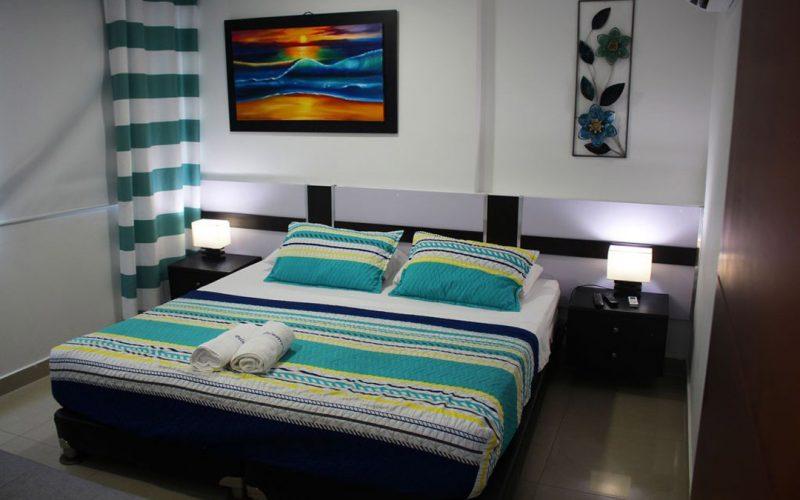 habitacion con cama doble negra y dos meses de noche con lamparas encendidas