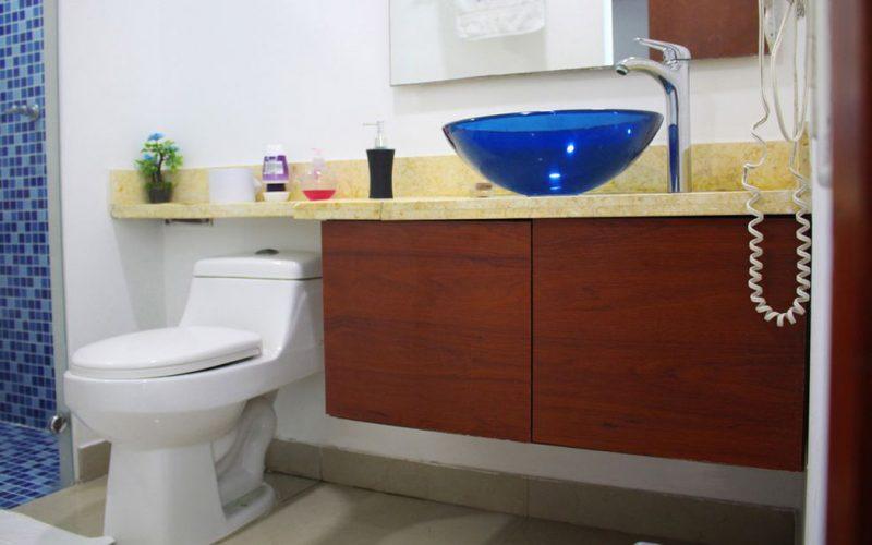 baño con inodoro blanco meson en piedra calisa y ducha con azulejos azules