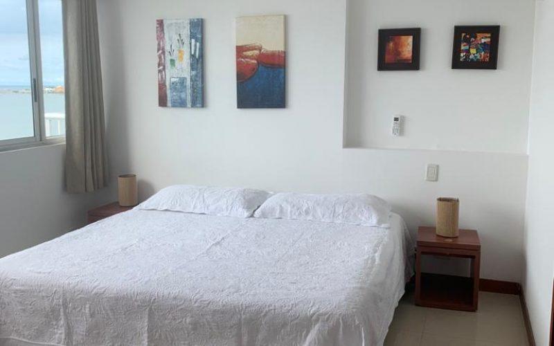 habitación con cama doble, nocheros y ventana con vista al mar en Cartagena