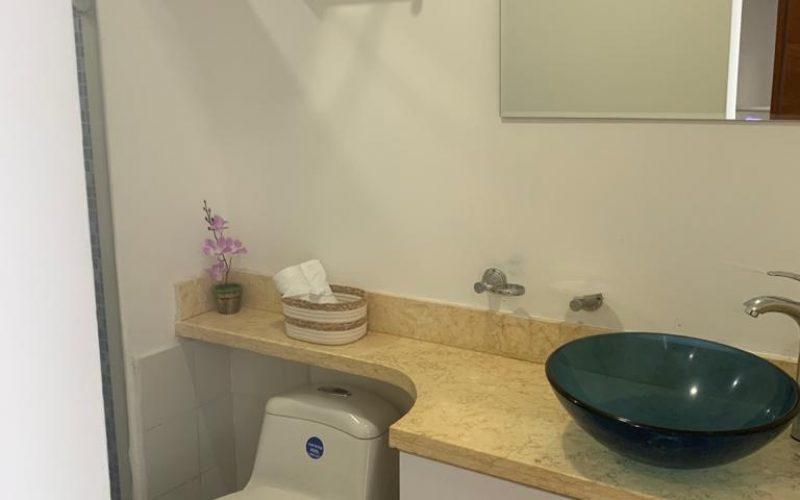 baño con lavamanos en vidrio sobre encimera de piedra y sanitario tradicional