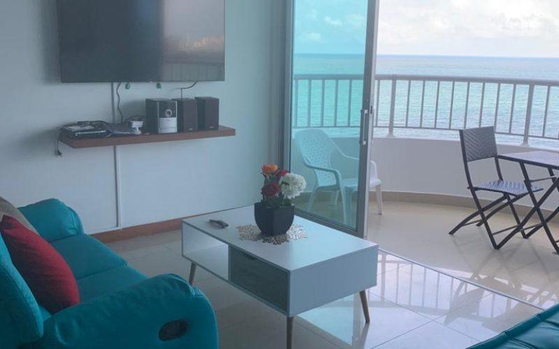 sala de estar con sofás, mesa de café y salida a balcón amoblado con vista al mar en apartamento de Cartagena