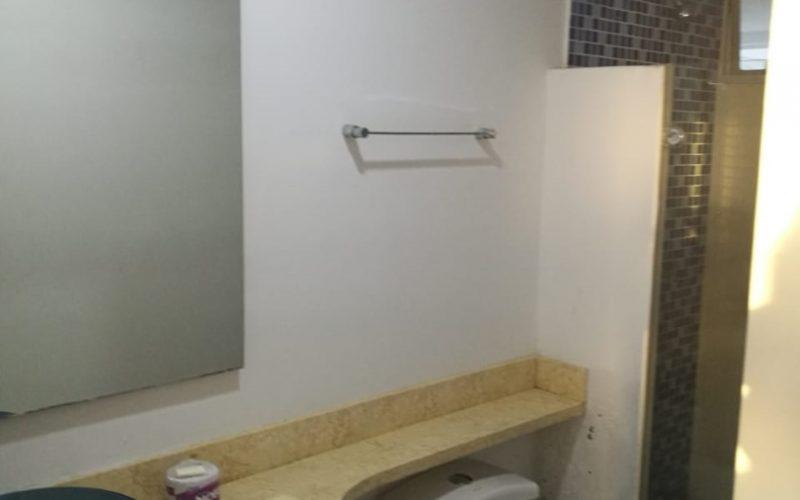 baño con lavamanos de vidrio sobre encimera de piedra, espejo, sanitario y ducha enchapada en azulejos azules