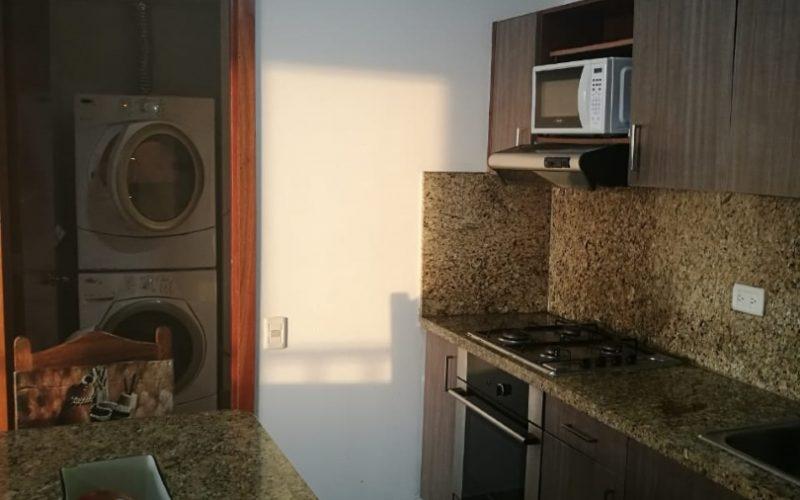 cocina tipo americano con barra comerdor y habitación de lavandería equipada