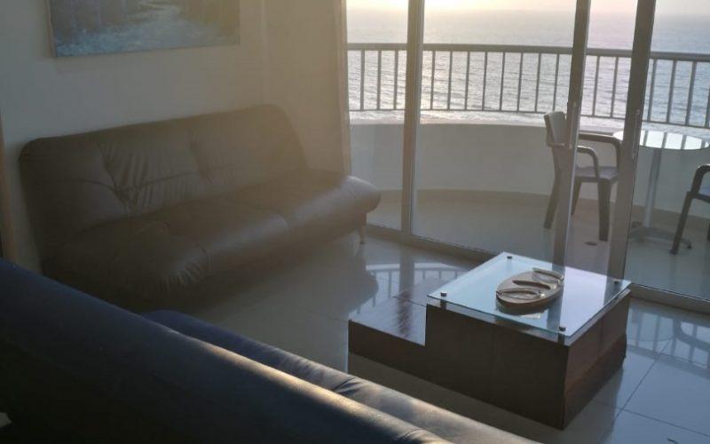 sala de estar amoblada con sofás y mesa de café tiene salida a balcón amobaldo con vista al mar de Cartagena