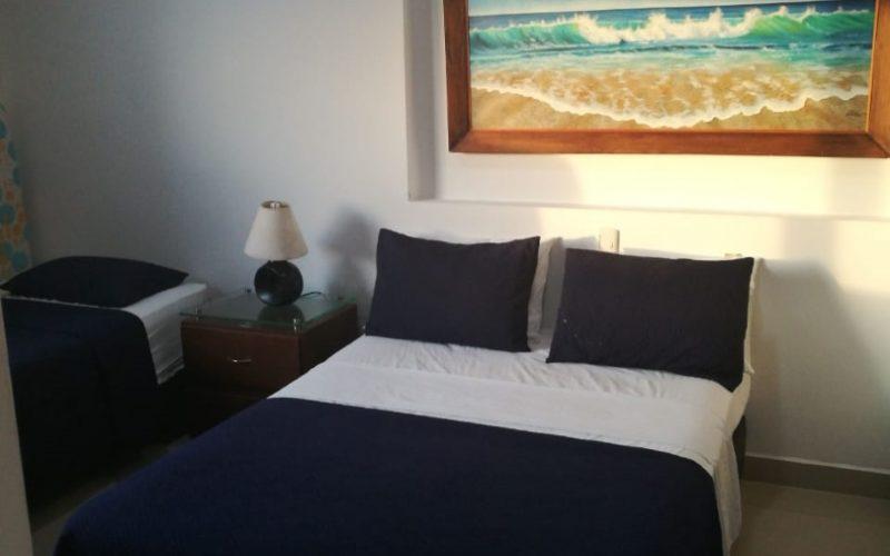 vista parcial de habitación con cama doble, cama sencilla y nochero