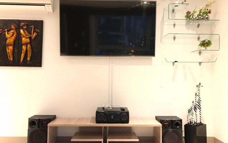 televisor plasma color negro en sala con cuadros de musicos y minicomponente