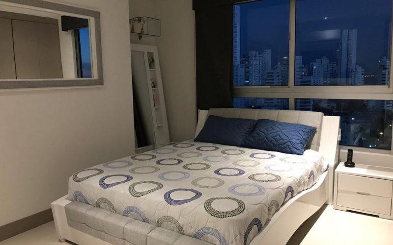 habitacion con cama doble color claro y mesa de noche blanca