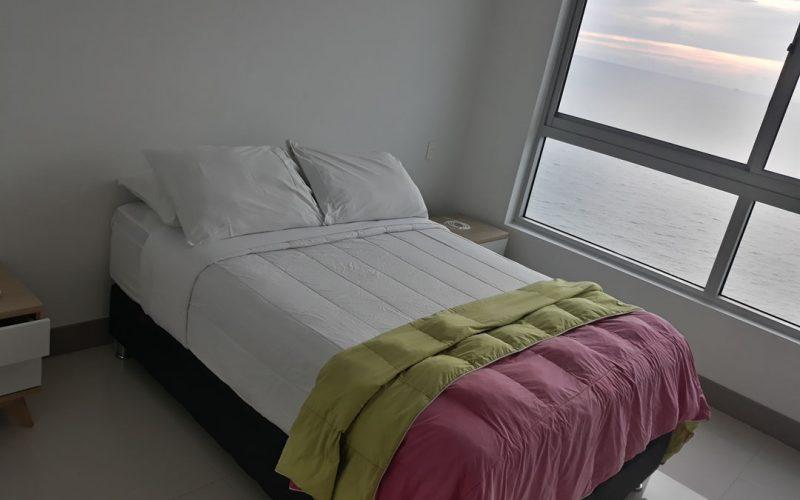habitacion con cama doble y mesas de noche con vista al mar de cartagena