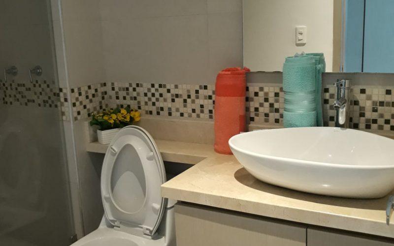 baño enchapado con cenefa color cafe y division de vidrio en la ducha