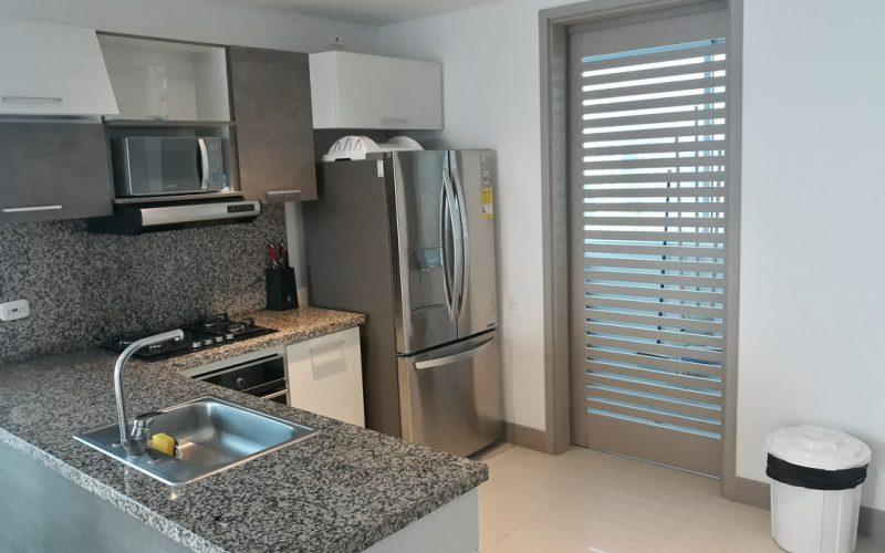 cocina enchapada con cajones grises y blancos estractor y microondas
