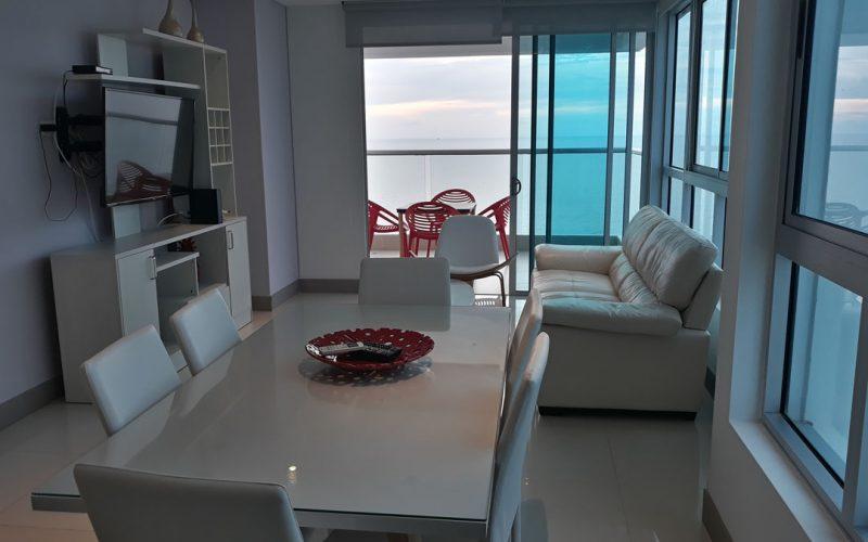 comedor en madera blanco con seis puestos y sala en cuero color blanco con televisor