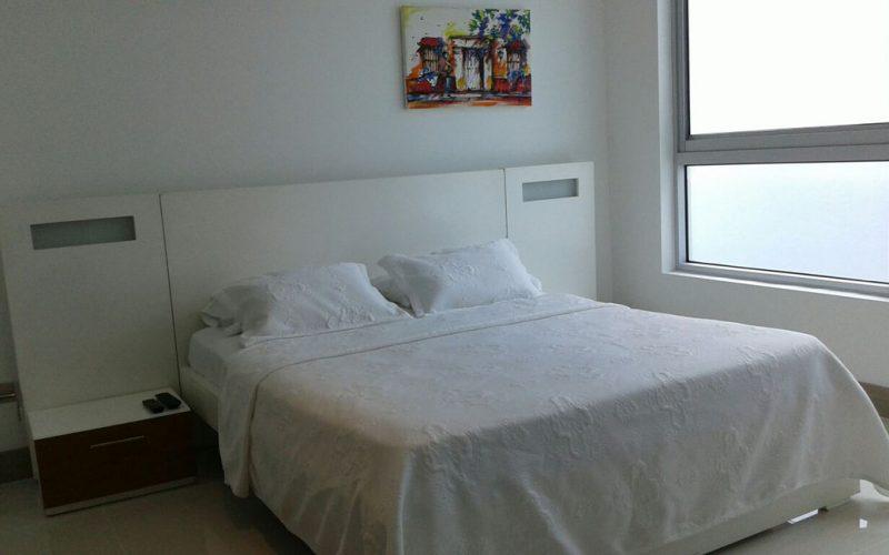 habitacion mediana con cama doble con tendidos blancos y nochero pequeño con ventana con vista al mar de cartagena