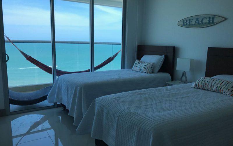 habitacion con dos camas sencillas con balcon, hamaca de colores y vista al mar