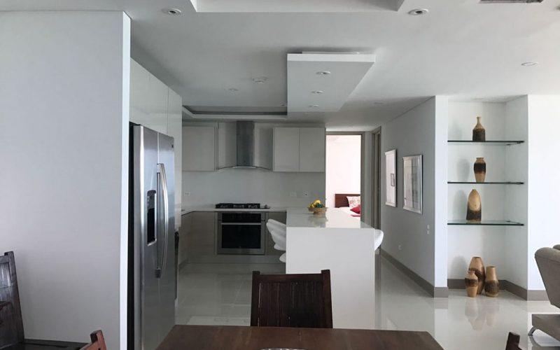 cocina con gabinetes blancos, horno, estractor de olores y isla para comer color blanca de para seis personas