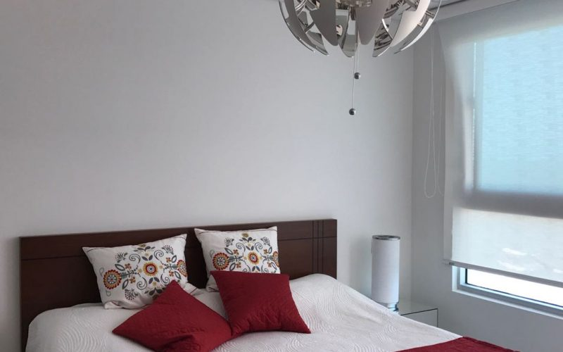 habitacion con cama doble en madera oscura y lampara redonda moderna en aluminio
