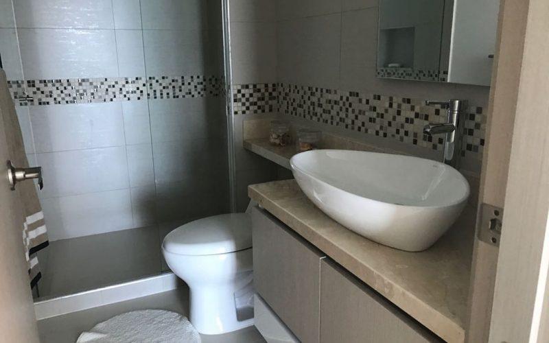 baño enchapado con lavamanos color blanco y mueble colgante
