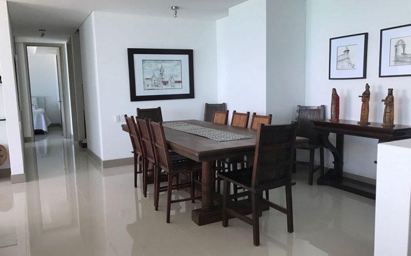 comedor en madera oscura para diez personas, piso color claro en porcelana con paredes blancas