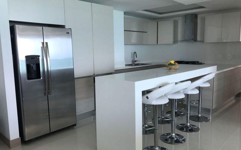 cocina terminada con gabinetes de color claro, nevecon y una isla color blanco para ocho personas