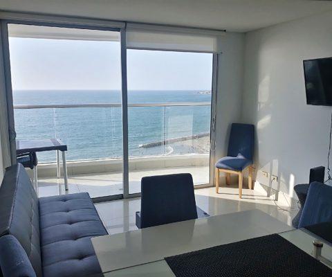desde el comedor de un apartamento se ve una sala amoblada de forma simple y un balcón que da vista a la playa
