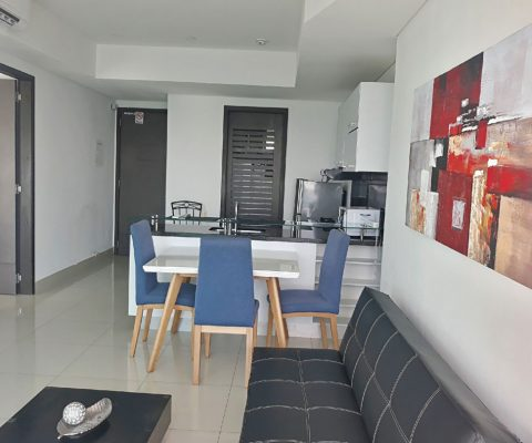 vista general de un apartamento, desde la sala de estar amoblada con sofá, hacia la cocina abierta y el comedor de 3 puestos