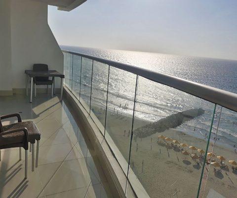 desde el balcón de un apartamento se puede ver abajo la playa de Bocagrande en Cartagena con sus sombrillas amarillas típicas