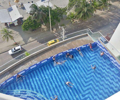 desde el balcón de un apartamento, se ve abajo, la piscina del mismo edificio y la avenida que cruzando lleva a la playa