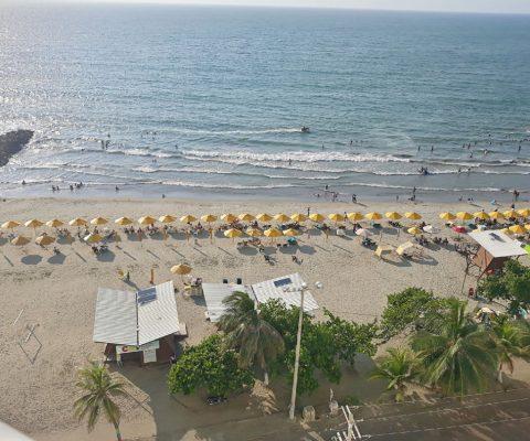 vista aérea de playa turística de Bocagrande en Cartagena, con sus típicas sombrillas amarillas y gran actividad de turistas