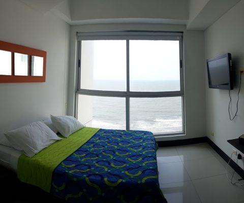 habitación con cama sin cabecero, tv en pared y ventanal piso techo que da vista al mar de Cartagena