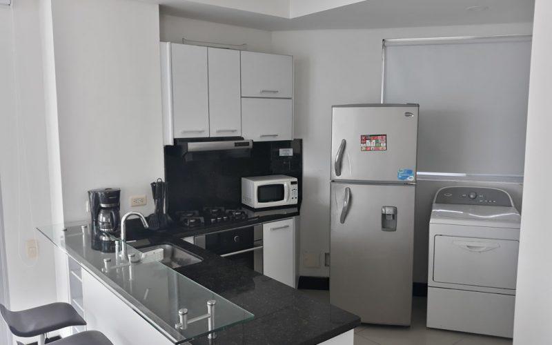 cocina abierta en colores blanco y negro, con barra en vidrio y butacas para 2 personas. equipada con nevera y lavadora