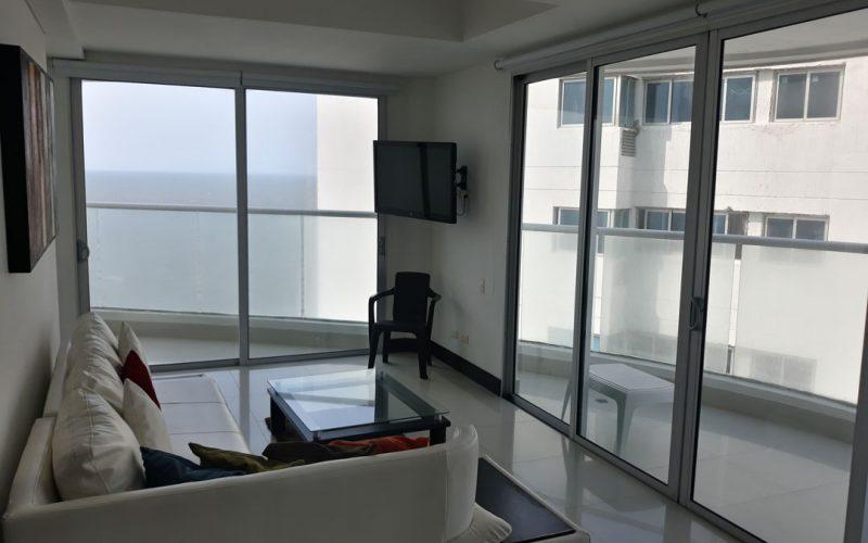 sala de apartamento con muebles, tv en pared y salida a amplio balcón con vista al mar de Cartagena