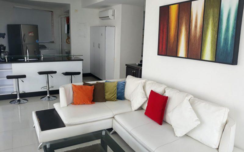 vista de apartamento con sala de estar amoblada con sofá en L y cocina abierta con barra y butacas para 3 personas
