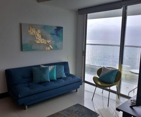 sala de estar con sofá y silla de estilo moderno. una puerta ventana da salida a un balcón con vista al mar de Cartagena
