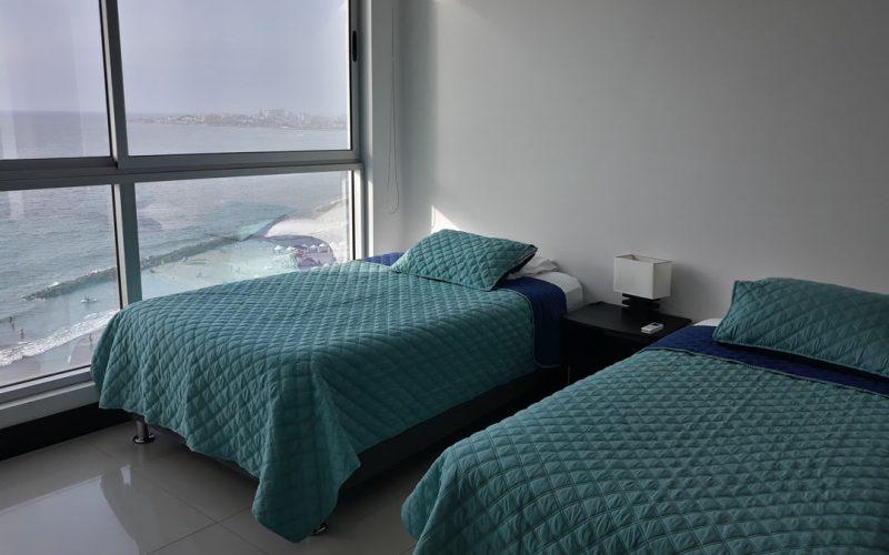 habitación de apartamento equipado con dos camas sencillas y nochero, su ventana da vista a la paya de Bocagrande Cartagena
