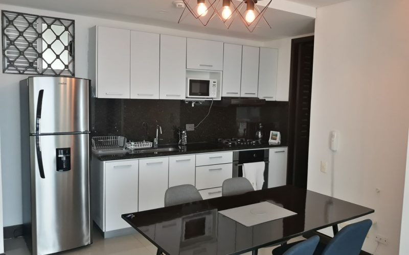 cocina abierta en colores blanco y negro acompañada de mesa de comedor en en vidrio y sillas para 4 personas