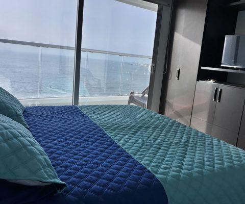 habitación con cama doble, armario y tv anidado. un ventanal de piso a techo da salida a balcón con vista al mar