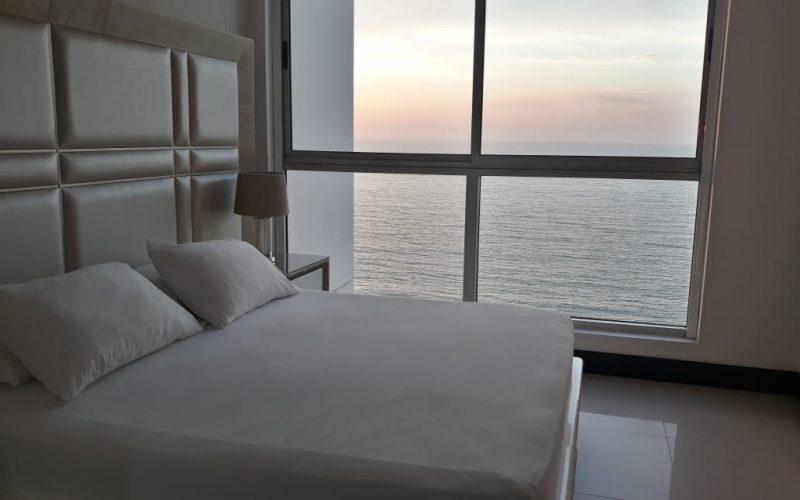 habitación con cama doble y nocheros de estilo elegante, un ventanal de piso a techo da una vista privilegiada del mar