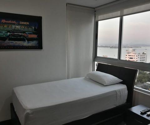 cama sencilla y nochero en habitación de apartamento con una ventana esquinera que da vista a la bahía de Cartagena