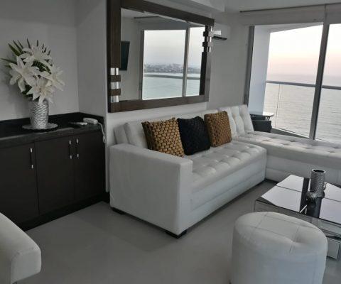 sala de estar de estilo elegante con muebles en cuero blanco y mesa de café, un ventanal da salida al balcón con vista al mar