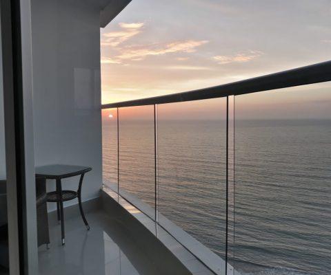 desde un balcón se puede ver en el horizonte el sol naranja de un atardecer sobre la bahía de Cartagena
