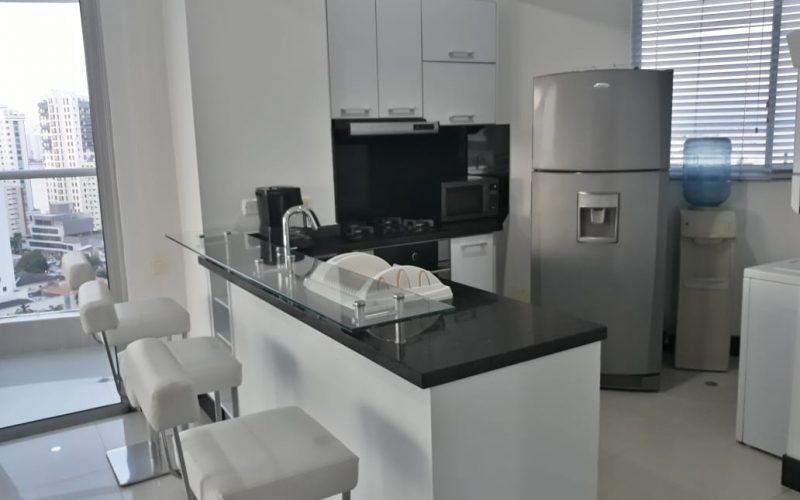 cocina abierta de estilo moderno con barra de vidrio y butacas para 3 personas, un ventanal da vista al balcón y la ciudad