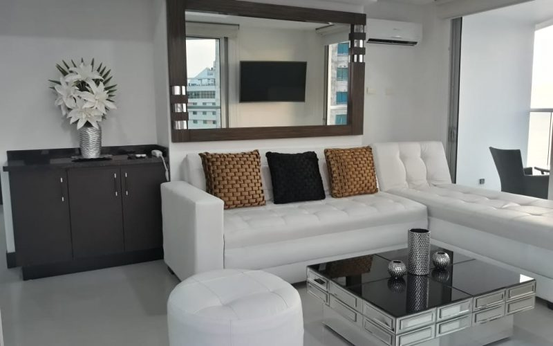 sala de estar amoblada con sofá en L de cuero blanco y mesa de café en vidrio color negro, el espacio es elegante y moderno