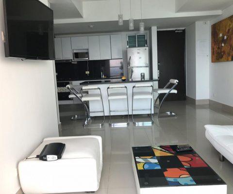 sala de estar con muebles blancos y tv, al fondo 5 butacas blancas acompañan un comedor tipo isla y una cocina abierta