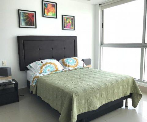 habitación con cama doble y 2 nocheros de estilo moderno, el ventanal piso a techo de la habitación da vista al mar