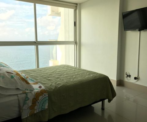 habitación con cama doble y tv plana, el ventanal piso a techo da una vista privilegiada sobre el mar de Cartagena