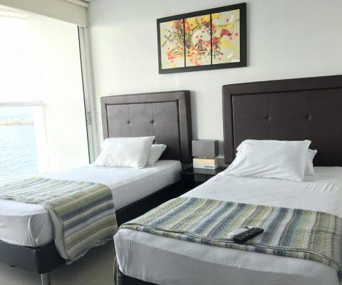 habitación equipada con 2 camas sencillas y nochero, la ventana piso a techo da salida a un balcón con vista a la playa